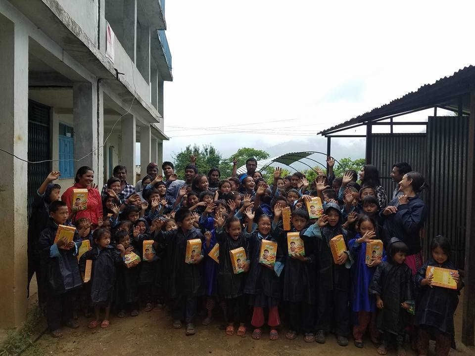 A group shot of the kids receiving raincoats