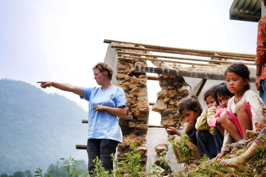 Architect Ruth with kids and damaged school behind