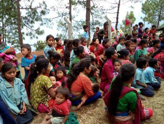 Mothers and children wait for a mid-day meal