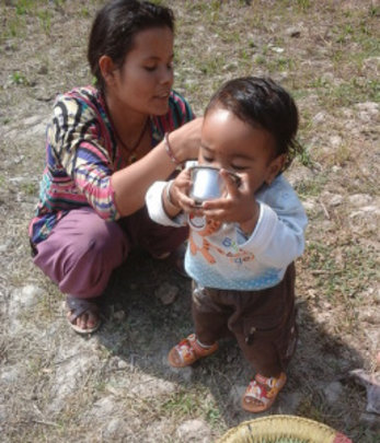 A small child drinking water from the filter