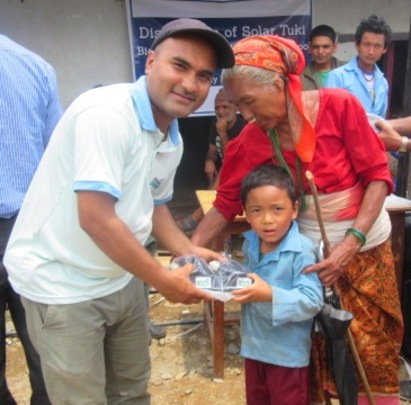 ECCA Program Officer distributing solar lamp