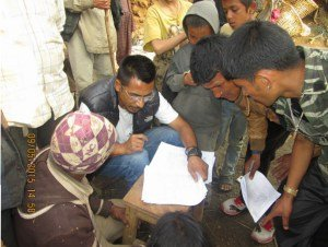 Forms being filled before relief distribution