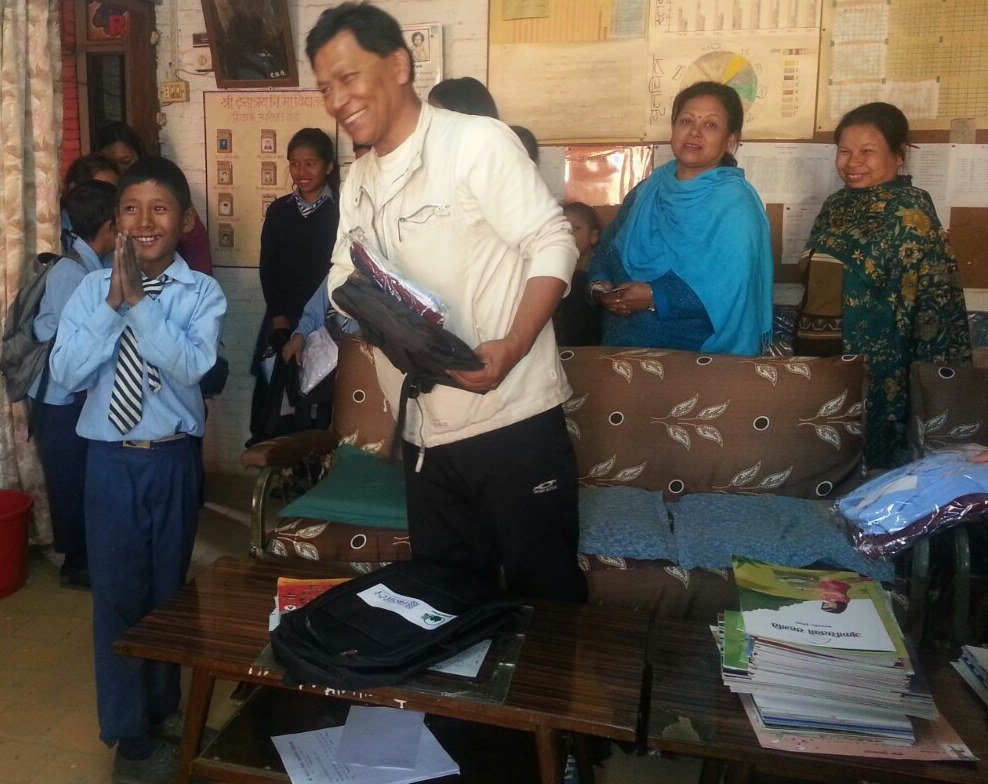 Dr Sainju from CONCERN distributes school supplies