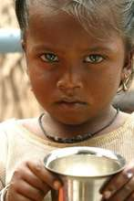 Slum girl holding a cup of milk