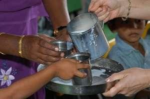 Western volunteers distribute milk at a slum schoo