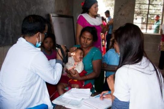 A doctor exams a child at an NRH outreach camp
