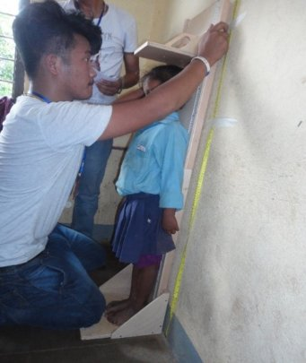 A staffer measures a young boy