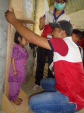 Standing tall...NYF staffer measurers a young girl