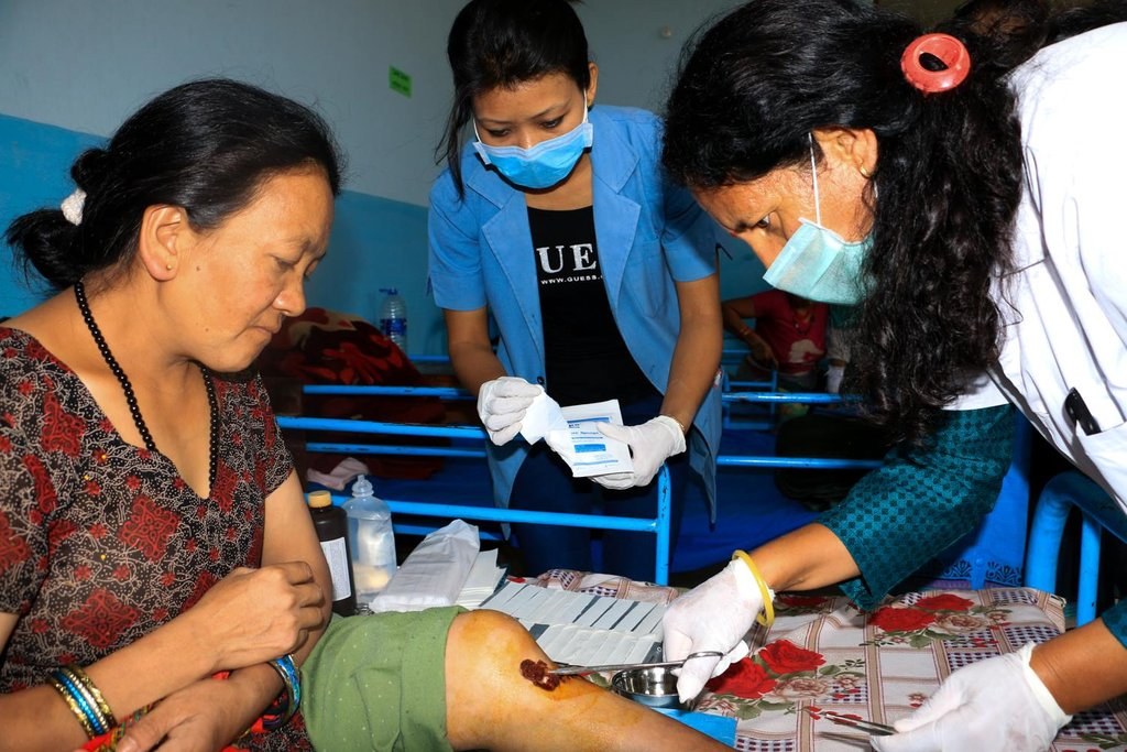 Health aides tend to injured earthquake victims