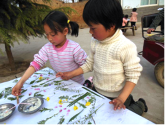 Children make a poster with twigs and leaves.