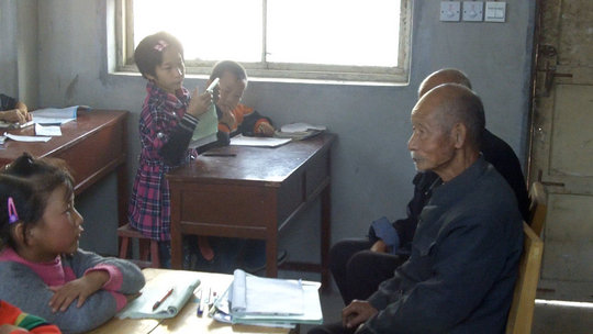 Students interview an elderly villager.