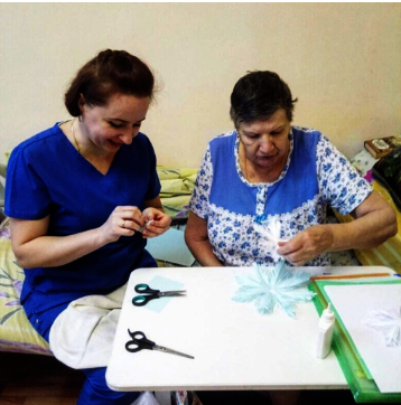 Care workers help with making decorations