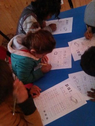 Younger children practising their writing
