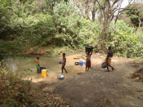 family collects drinking water from a stream
