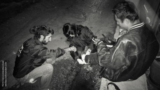Offering first aid to a homeless young man
