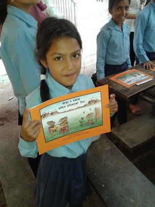 A girl at refugee camp shows her copy of the book