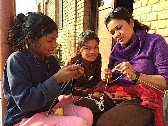 Sunita (L) learns to knit from Uma Auntie