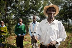 Students instructing local farmer on composting