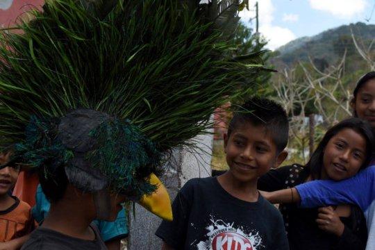 Children wear Quetzalo's mask