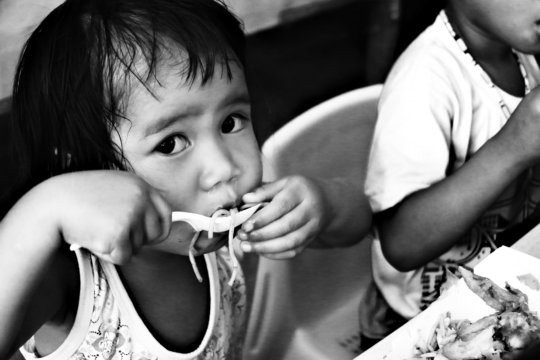 Her three-year old child eats her food with gusto.