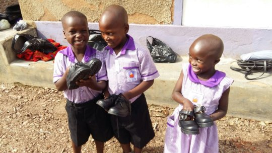 Nyaka Primary students holding their new shoes