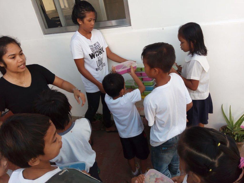 Volunteers distributing the kids lunchboxes