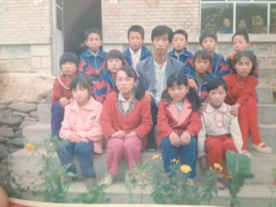 Xiaojie with her teacher and classmates in school