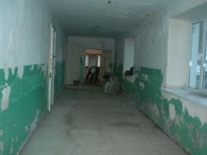 Floor in the hallway, bathroom is seen in the back