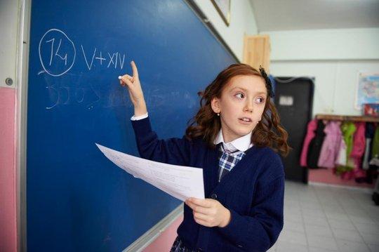A girl student writing on the blackboard