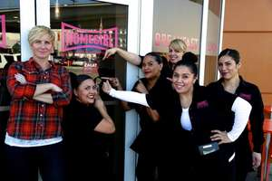 Homegirl Cafe staff pointing to our Zagat sign