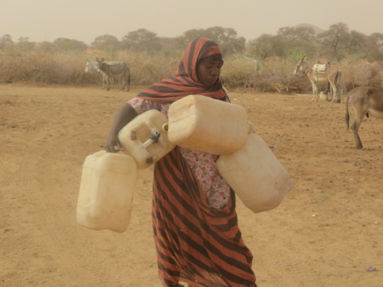 Woman walking to water with jerry cans.