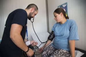 A health worker checks Roumatsh's blood pressure