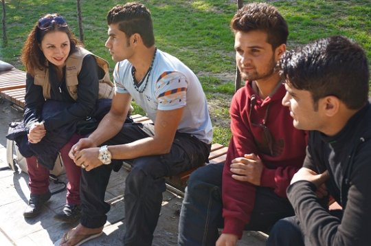 Sanja speaking with three young men