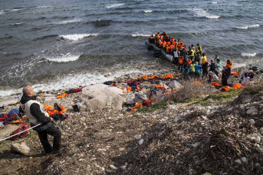 Vaios helping refugees climb from their raft