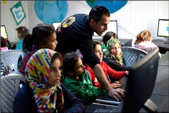 A Jordanian volunteer teaches computer skills.