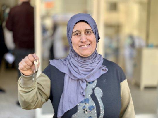 Khadija holding her house key from Syria