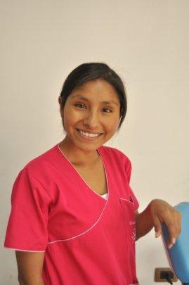 Aracely smiling in her bright dental uniform