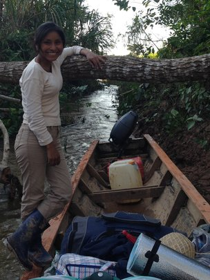 Aracely taking canoe up shady jungle rivelet