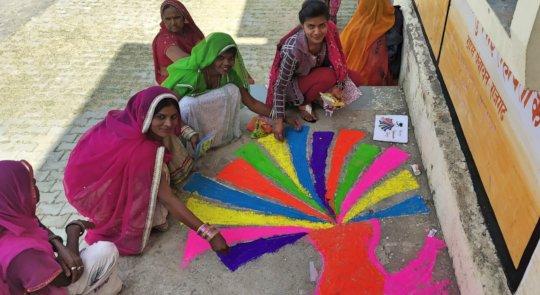 Women Making Colorful Rangoli