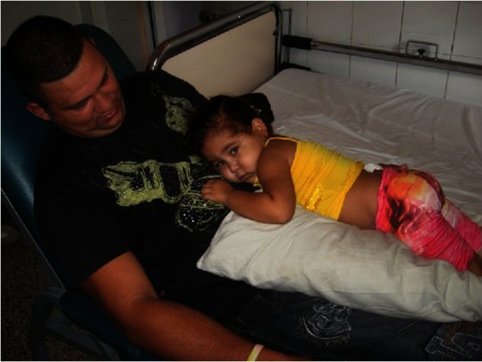 A father comforts his young daughter at bedside