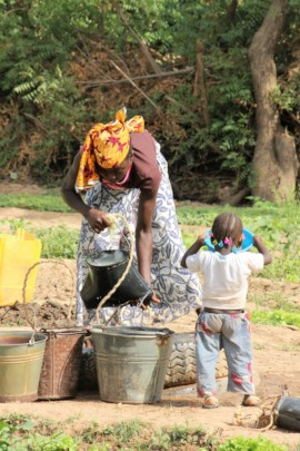 A mother and child work side-by-side in the garden