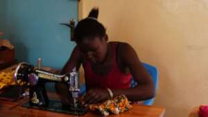 A beneficiary at the GEC sewing a shopping bag