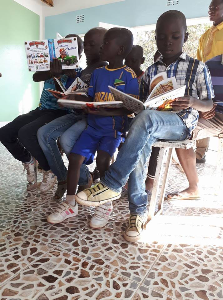 Reading in their new classroom at Maison Kimbilio