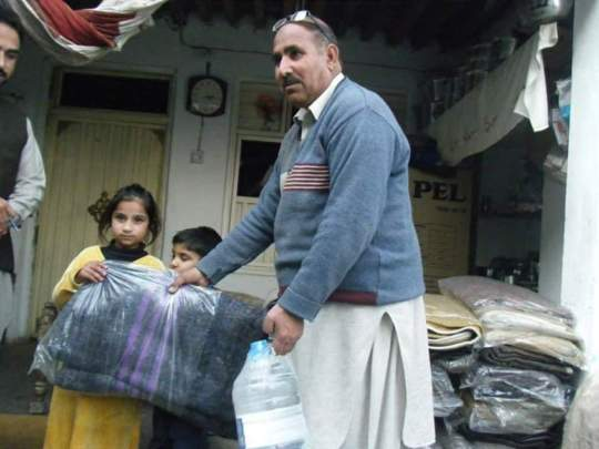 Kainats Dad handing a blanket to an orphan