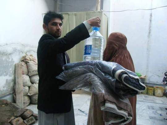 Kainat's brother handing blankets/water to a widow