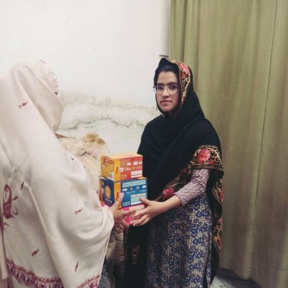Kainat handing over biscuits and food to a widow