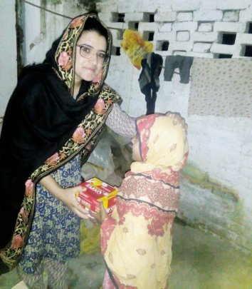 Kainat giving food supplies to an orphan