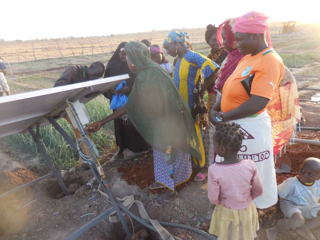 Women showing how they operate the pump