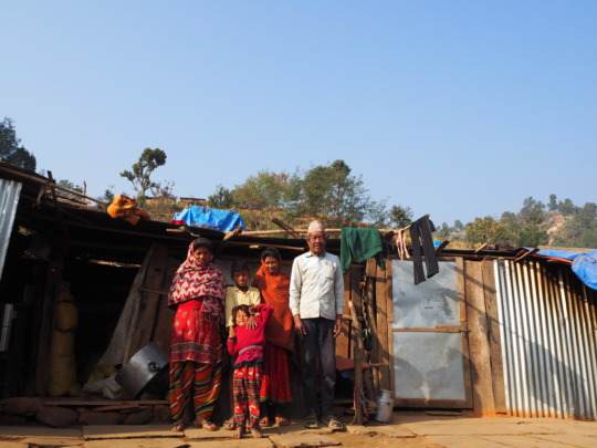 Beneficiary Family in front of Makeshift Shelter