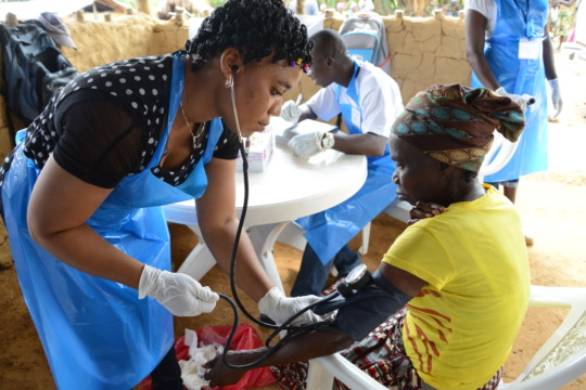 A nurse checks the blood pressure of a patient